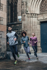 Group of young friends running on Barcelona streets.