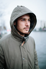 Portrait of a lonely man standing next to an inner city canal during bad weather