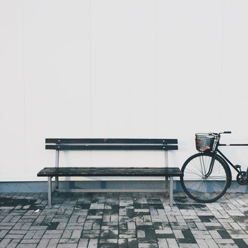 Old bike and bench in front of the white wall
