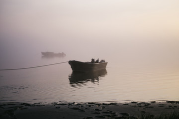 Fishing boats in the water on a foggy morning