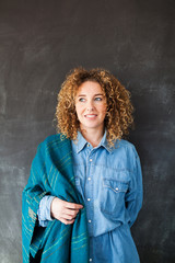 Portrait of a young beautiful woman with a blue scarf and curly hair