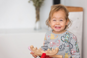 One and a half year old baby girl swinging on the red moose wooden toy