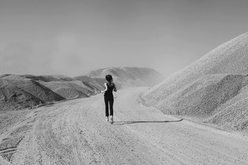 Black and white photo of a girl running in the desert