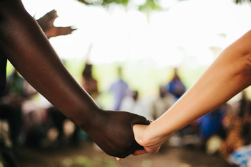 African Woman and American Woman Hold Hands in Uganda
