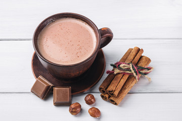 Hot cocoa with milk in brown clay cup, broken chocolate cubes, hazelnut and cinnamon sticks on white wooden planks