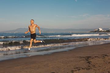 Active senior man - in great shape - running shirtless on beach in morning sunshine