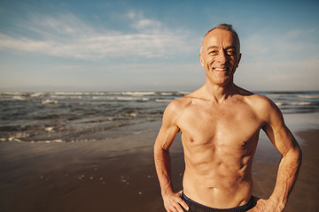Active senior man - in great shape - smiling shirtless on beach in morning sunshine