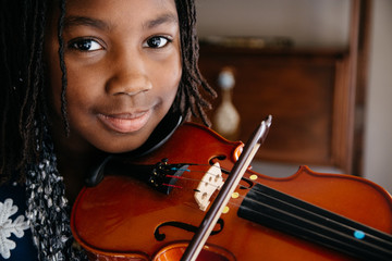 Smiling black girl playing a violin