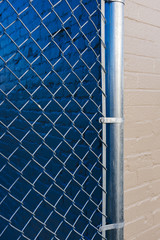 Chain-link fence in front of painted wall