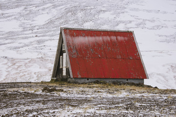 A refuge hut with red steeply pitched roof, in a snowy landscape.