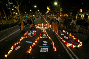 """Demonstrators light candles arranged to read """"Peace"""" during a protest against the imprisonment of leaders of two of the largest Catalan separatist organisations, in Barcelona"""