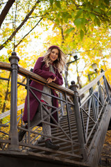 Autumn walk in the park. Girl on the stairs. Good mood and fun.