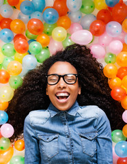 Young african woman playing with many colorful balloons.