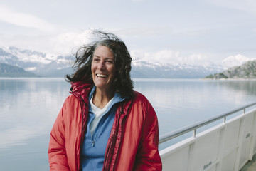 Happy middle-aged woman on tour boat, Muir Inlet and Glacier Bay NP in distance