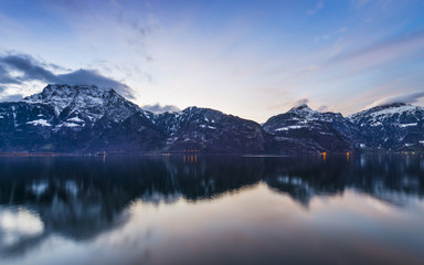 Poster Reflexion Bright sunset colors. Swiss Alps. Colorful sunset over the mountains and lake. Tops in the snow reflected in lake water.