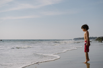 boy stands on his tip toes at the edge of the water