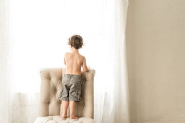 A Little Boy With No Shirt Looks Out A Window