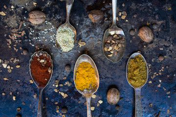 Metal spoons with colorful spices
