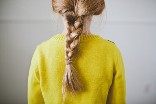 Rear view of child with braid and yellow sweater