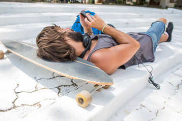 Young caucasian man lying down on his skateboard checking phone