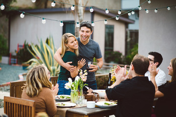 Couple making an announcement at a backyard dinner party.