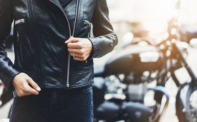 Girl in black leather jacket on background motorcycle in sun flare atmospheric city, hipster biker female hands closeup, motorbike street lifestyle, traveler bike route in summer holiday concept