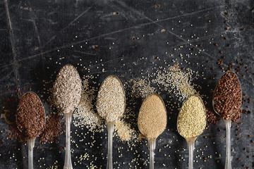 Various health seeds and grains arranged in vintage spoons
