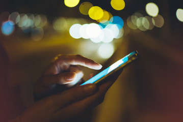 Girl pointing finger on screen smartphone on background illumination glow bokeh light in night atmospheric city, hipster using in hands mobile phone, mockup lights street, online internet concept