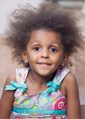 Portrait of young girl of mixed race  with frizzy fuzzy brown hair smiling sweetly