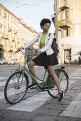 Young black woman portrait on a bicycle in the city