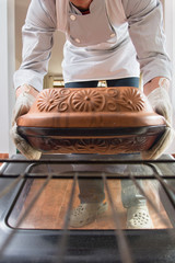 Male chef holding a clay pot with food preparing to put in in the oven