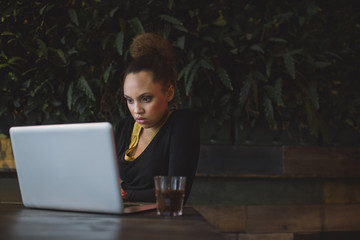 Young businesswoman using laptop at cafe