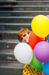 Portrait of happy ginger woman with balloons around her