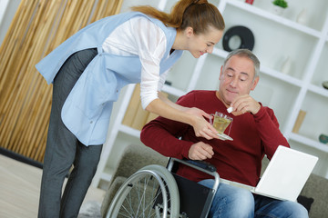 female carer giving medicine to senior man at home