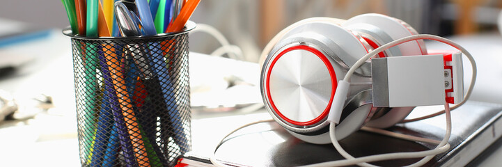 Headphones diary and pencil lie on the desk of the concept