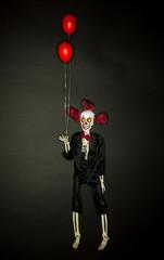 Als unheimlicher Clown bemalte Skelettpuppe mit roten Luftballons