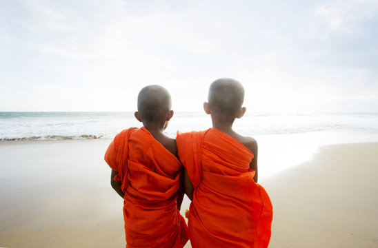 Rear view of two young Buddhist monks at beach, Sri Lanka