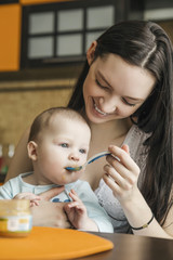 Smiling young woman feeding baby daughter