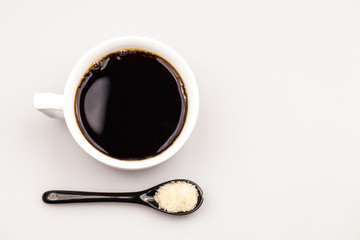 White coffee cup with coffee and black teaspoon with brown sugar