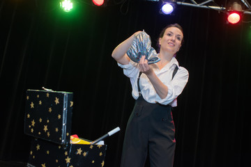 young beautiful magician on stage during show