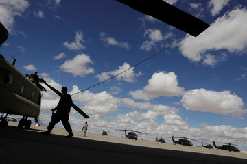 A soldier from the 1st Armored Division, Combat Aviation Brigade, works to disassemble a CH-47 Chinook helicopter to ship to Puerto Rico in order to aid in recovery efforts following Hurricane Maria at Fort Bliss in El Paso