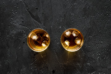 shots of whiskey with ice on black bar table background top view mock up