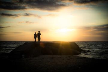 夕焼けの海を散歩するカップル