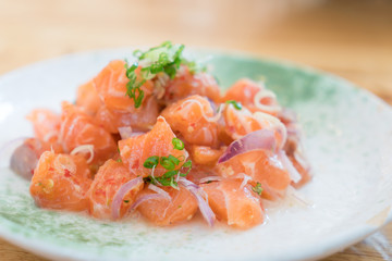Japan salmon spicy salad with herbs. Mix Japanese and Thai food between Japan salmon sashimi and Thai herb in Japanese restaurant..