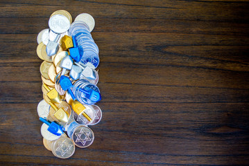 pile of tiny dreidels with gold and sliver Hanukkah coins on a wooden table with copy space