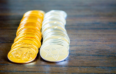 2 parallel rows of gold and silver Hanukkah coins on a wooden table with copy space