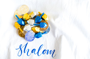 pile of tiny dreidels with gold and silver Hanukkah coins on a white cloth with the word Shalom on it