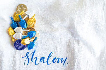 pile of tiny dreidels with gold and silver Hanukkah coins on a white cloth with the word Shalom on it with copy space