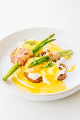 Eggs benedict with bacon twist asparagus