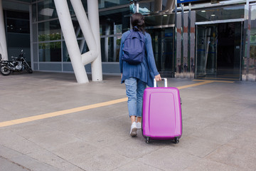 Woman traveller with travel suitcase or luggage walking in airport terminal